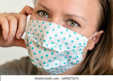 Portrait of woman wearing handmade cotton fabric face mask. Protection against saliva, cough, dust, pollution, virus, bacteria, COVID-19.