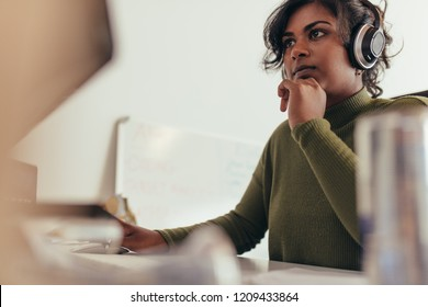 Portrait of woman wearing headphones looking at computer monitor. Female computer programmer working at her office desk.