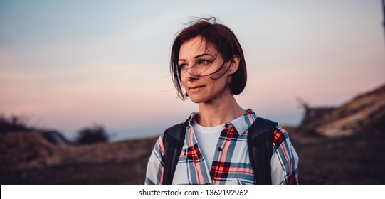 Portrait of woman wearing plaid shirt on the mountain top and looking into distance