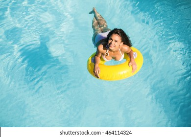 Portrait of woman in white bikini floating on inflatable tube in swimming pool on a sunny day