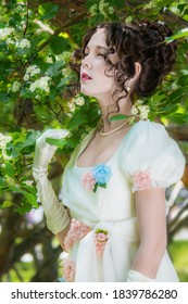 Portrait woman in white bride dress near blooming tree.