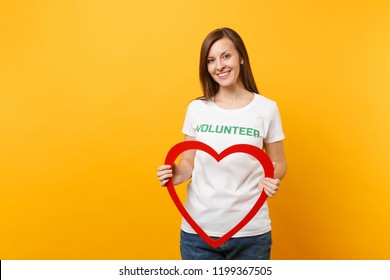 Portrait of woman in white t-shirt with written inscription green title volunteer hold big red wooden heart isolated on yellow background. Voluntary free assistance help, charity grace work concept