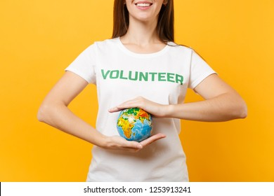 Portrait of woman in white t-shirt with written inscription green title volunteer hold in palms Earth world globe isolated on yellow background. Voluntary free assistance help, charity grace concept