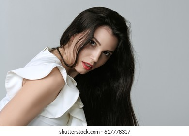 Portrait of a woman who is leaning forward and showing curvy hair. She has daytime makeup, perfect skin and long dark hair