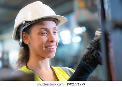Portrait of woman worker beautiful face with eye confident and wearing working suite dress and safety helmet at heavy machine in industry factory. Brazilian worker concentrate on workplace.