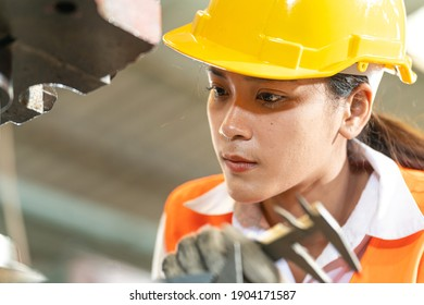 Portrait of woman worker beautiful face with eye confident and wearing working suite dress and safety helmet at heavy machine in industry factory. Asian female worker concentrate on workplace.