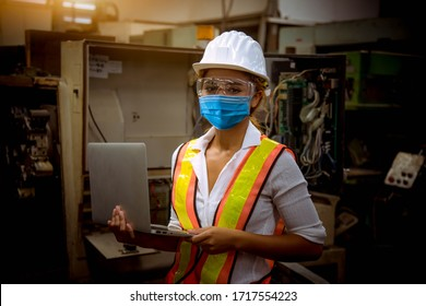Portrait woman worker under inspection and checking production process on factory station by wearing safety mask to protect for pollution and virus in factory.
