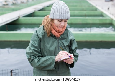 Portrait of woman working on fish farm, making notes in notebook outdoors