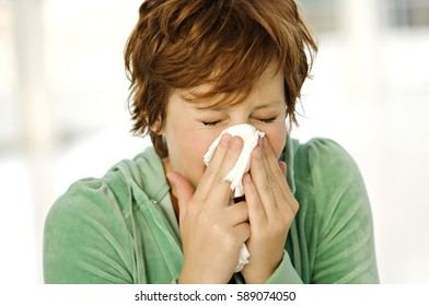 Portrait of womanwith allergy blowing her nose