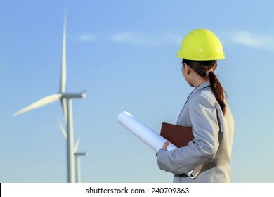 portrait women asia engineer working and holding blueprints at wind turbine farm Power Generator Station