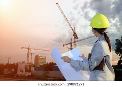 portrait women asia engineer working and holding blueprints at construction site