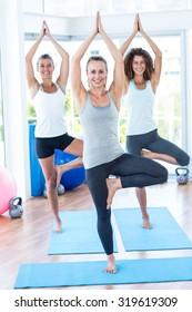 Portrait of women doing tree pose in fitness studio on yoga mat
