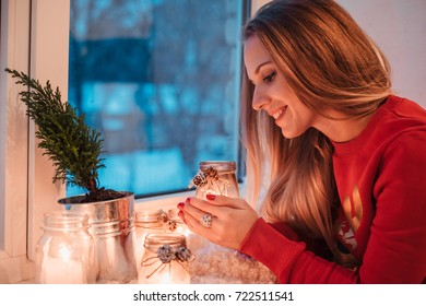 Portrait of women looking at candles and dreaming on the windowsill at winter. Cozy place at home. Happy holidays