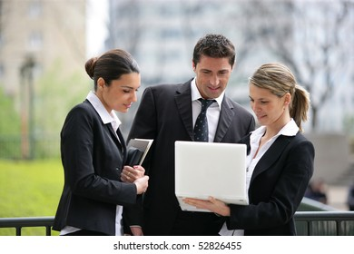 Portrait of women and a man in front of a laptop computer