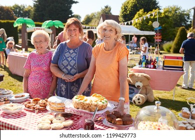 Portrait Of Women Serving On Cake Stall At Busy Summer Garden Fete