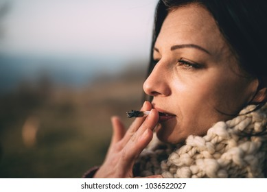 Portrait of women wearing knitted scarf smoking outdoors