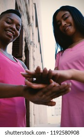 Portrait of women wearing pink for breast cancer and putting hands together in park