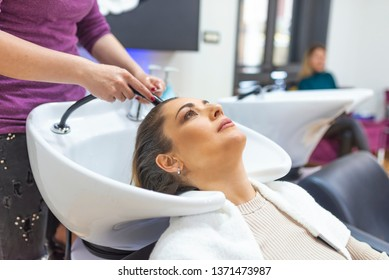 Portrait of women which wash hair in a beauty salon. Beautiful woman getting a hair wash. In a salon. Girl in a beauty salon. wash your hair, hair care, health.