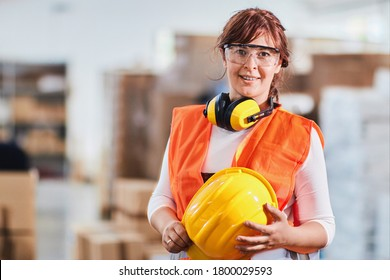 Porträt einer Arbeitnehmerin in einer Fabrik mit Schutzbekleidung