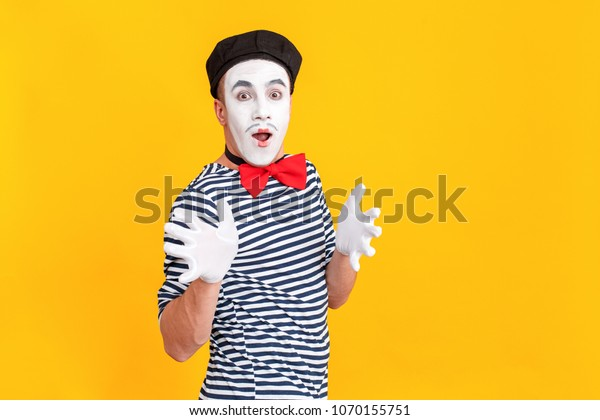Portrait of wondered mime man looking at camera, little smile. Emotions and feelings concept. Indoor shot, yellow background
