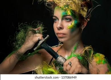 Portrait of the wood beauty looking afar with a dagger in a hand close up