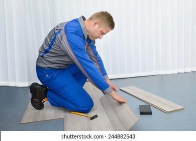 Portrait Of A Worker Assembling New Laminate Floor