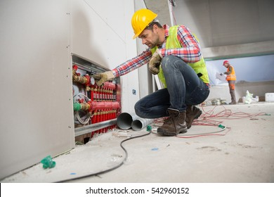 Portrait of a worker, constructing and checking development of a small business hall. Reliable civil engineer working on a construction site, foreman at work, another man in the background