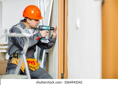 Portrait of a worker with electrical screwdriver. Repair and building concept.
