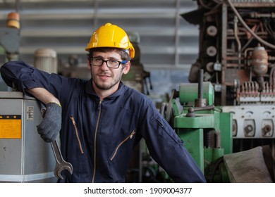 Portrait of a worker in a factory. Portrait of industrial worker indoors in factory. Young technician with hard hat.
