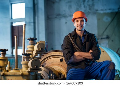 Portrait of a worker in the helmet near the steam turbine