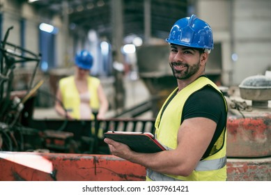 Portrait of worker man with tablet and woman in background