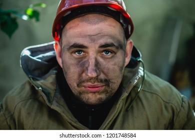 Portrait of the worker, a miner or Metallurgist in the orange helmet outside.