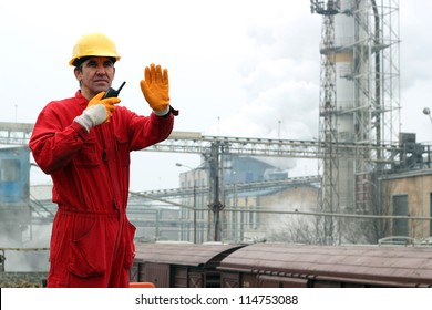 A portrait of a worker in red overalls and yellow helmet.