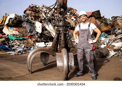 Portrait of worker standing by hydraulic industrial machine with claw attachment used for lifting scrap metal parts in junk yard.
