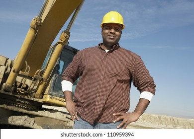 Portrait of a worker wearing hardhat in front of a crane at construction site