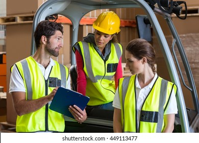 Portrait of workers are looking a clipboard in a warehouse