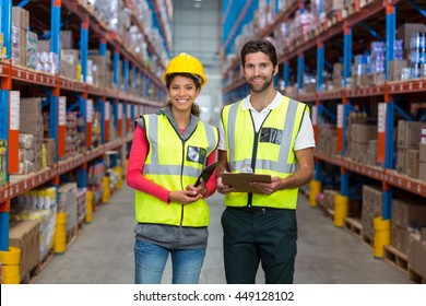 Portrait of workers are posing and smiling to the camera in a warehouse
