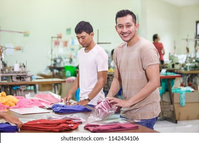 portrait of workers at textile factory packaging their products while smiling