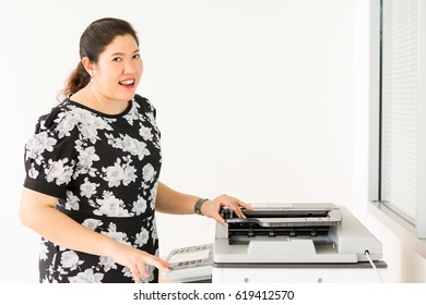 Portrait working woman: She is doing copy documents at photocopier. Beautiful plump woman is a secretary or employee of company or office. Pretty girl get satisfied or love her job. She work at office
