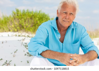 Portrait of a worried concerned thoughtful attractive handsome senior man sitting down outside on a beach and smiling