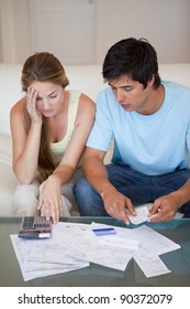 Portrait of a worried couple looking at their bills in their living room