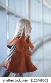 Portrait of worried little girl wearing striped dress and coat