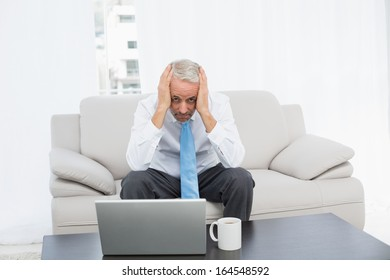 Portrait of a worried mature businessman with head in hands in front of laptop in the living room at home