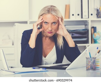 Portrait of worried mature female manager working on laptop in office