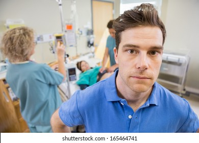 Portrait of worried mid adult man with nurses examining pregnant woman in background at hospital