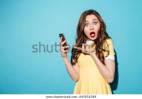 Retrato de una guapa preocupada vestida apuntando a un teléfono móvil y mirando la cámara aislada sobre fondo azul