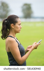 Portrait worried sad sporty beautiful young hispanic woman using smart phone, networking, texting, chatting in park outdoor after exercising, blurred background.