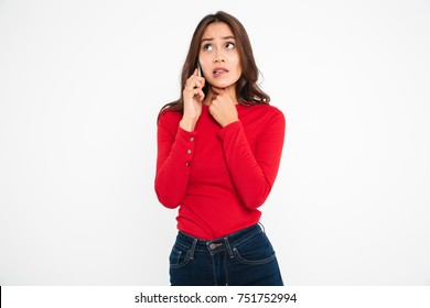 Portrait of a worried scared asian woman talking on mobile phone while standing and looking away isolated over white background