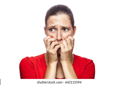 Portrait of worried scared woman in red t-shirt with freckles. looking at camera, studio shot. isolated on white background.