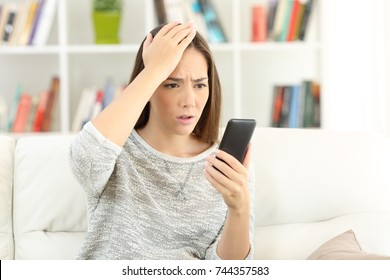 Portrait of a worried woman making mistake on a smart phone sitting on a sofa at home